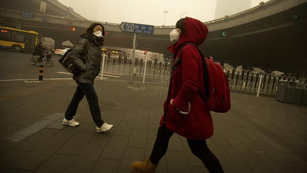 Pedestrians wearing face masks walk past an elevated highway amid heavy pollution and fog in Beijing (AP)