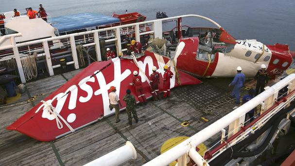 Crew members of the Crest Onyx recovery ship prepare to unload the recovered tail section of crashed AirAsia Flight 8501 (AP)