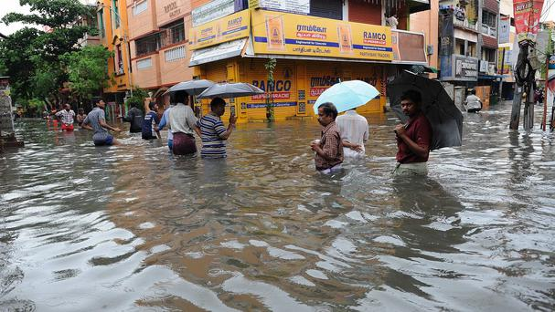 People wade through a flooded street in Chennai, southern Indian (AP)