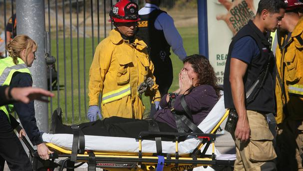 A victim is wheeled away on a stretcher following a shooting that killed multiple people at a social services facility in California (David Bauman/The Press-Enterprise via AP)