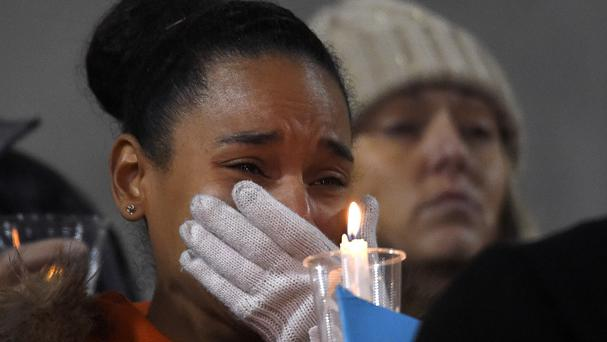 A woman grieves for the shooting victims during a candlelight vigil at San Manuel Stadium in San Bernardino (AP)