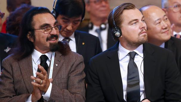 Leonardo DiCapri with his father George listening to speeches at Paris City Hall (AP)