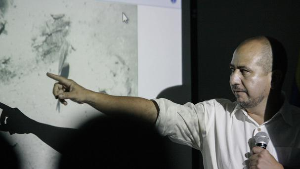 Ernesto Montenegro, director of the Colombian Institute of Anthropology and History of Colombia, shows a picture of remains of the Galleon San Jose (AP)