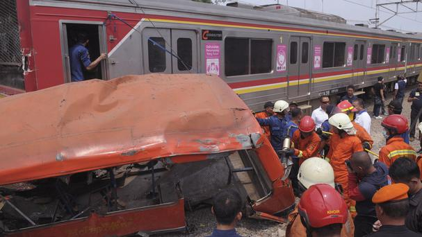 Rescuers remove the wreckage of a passenger minibus after it was hit by a commuter train near Jakarta (AP)