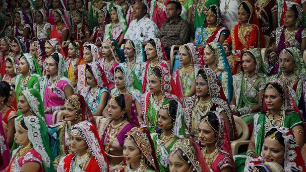Indian diamond trader Mahesh Savani (top centre) paid for 151 brides to be married