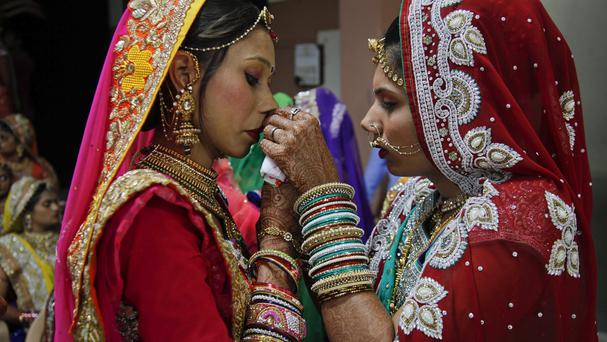 An Indian bride helps another with her attire during a mass wedding (stock image)