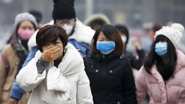 A woman uses her hand to cover her face from pollutants as people walk along a street on a polluted day in Beijing (AP)