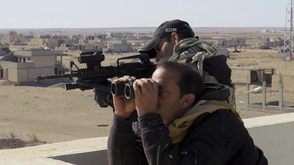 Iraqi anti-terrorism forces watch a military operation to regain control of the western suburbs of Ramadi (AP)