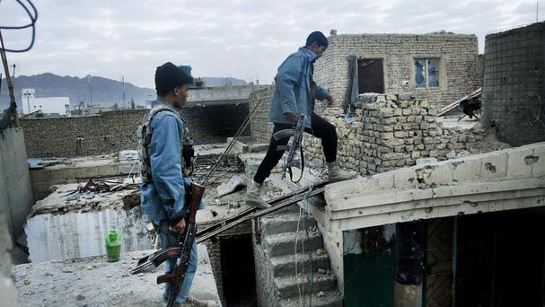 Afghan security forces inspect damages after clashes between police and Taliban militants (AP)