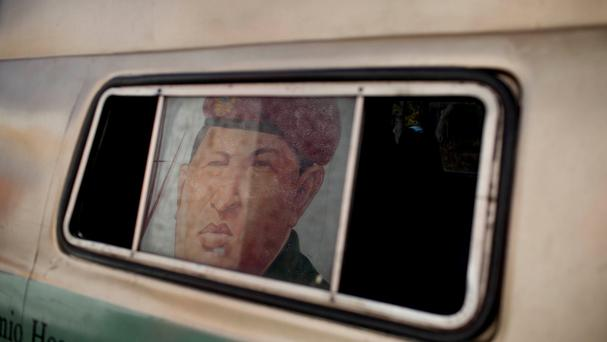 An image of Venezuela's late president Hugo Chavez decorates a bus window in the 23 de Enero neighborhood of Caracas (AP)