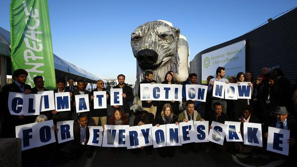 Activists from Greenpeace stage a protest in front of a mechanically operated polar bear in Le Bourget, north of Paris. (AP)