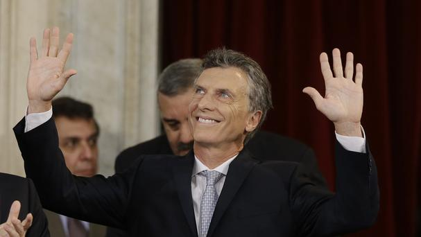 Mauricio Macri waves after being sworn in as new president at the Congress in Buenos Aires. (AP)