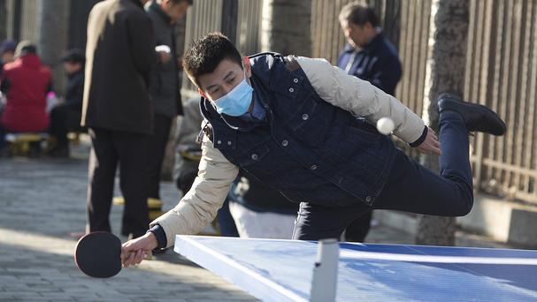 A man wears a mask as he plays table tennis or ping pong at a park in Beijing, China (AP)