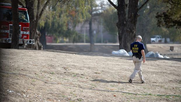 An FBI bomb specialist walks by Seccombe Lake in San Bernardino, California (Micah Escamilla/The Sun via AP)