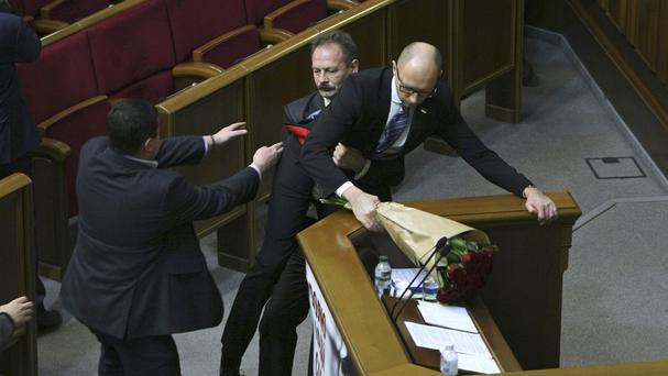 Oleh Barna tries to pull prime minister Arseniy Yatsenuk away from the podium (AP)