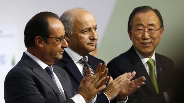 French President Francois Hollande, left, French foreign minister Laurent Fabius, centre, and United Nations Secretary-General Ban Ki-moon applaud at the COP21 (AP)