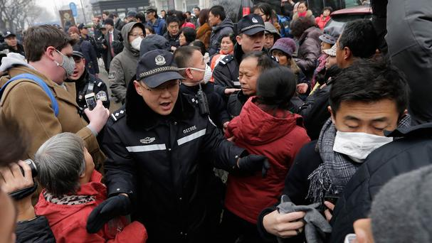 Police officers push away supporters of rights lawyer Pu Zhiqiang and foreign journalists near the No 2 Beijing Intermediate People's Court (AP)