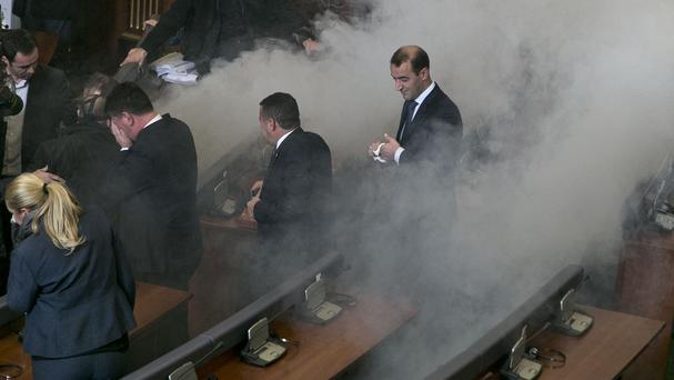 Lawmakers react as opposition lawmakers release tear gas canisters, disrupting a parliamentary session in Kosovo capital Pristina (AP)