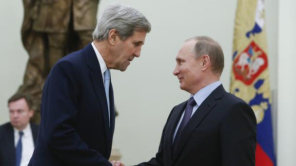 Russian president Vladimir Putin shakes hands with US secretary of state John Kerry during their meeting in the Kremlin (Sergei Karpukhin via AP)