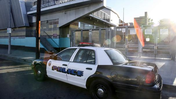 A police car is parked outside of Miguel Contreras Learning Complex in Los Angeles (AP)