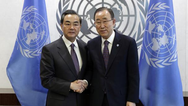 China's foreign minister Wang Yi, left, poses for photos with UN secretary general Ban Ki-moon before their meeting at the United Nations (AP)