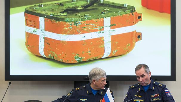 Russian generals talk as an image of the flight data recorder from the Russian warplane is displayed on a screen in the background (AP)