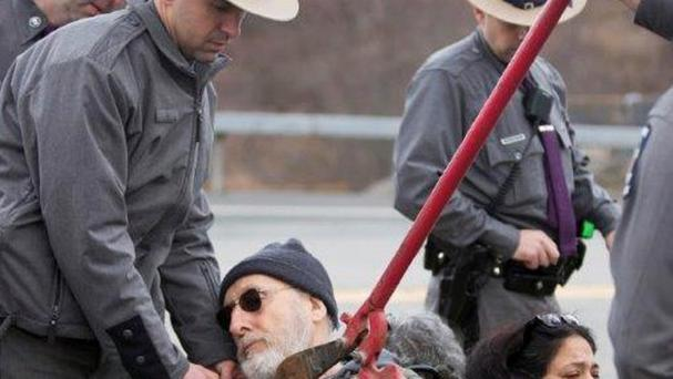 Police use bolt cutters to remove an interlocking device around James Cromwell's neck during the protest (Times Herald-Record/ AP)