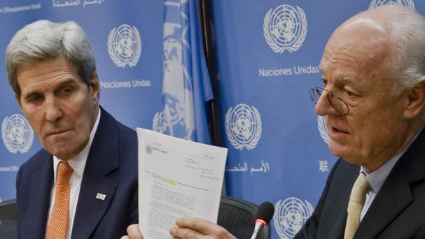 UN special envoy for Syria Staffan de Mistura, right, shows US secretary of state John Kerry a copy of the Security Council resolution (AP)