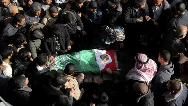 Palestinian relatives gather around the body of Mohammed Alagha, 20, during his funeral in Khan Younis City, Gaza, after he was killed during clashes with Israeli soldiers (AP)