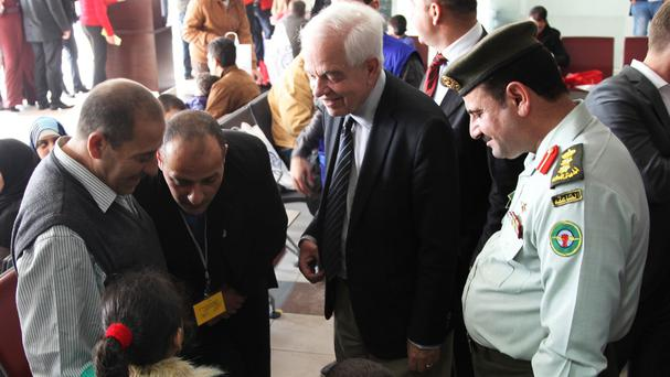 Immigration minister John McCallum, second from right, talks to a Syrian family leaving Jordan to live in Canada (AP)