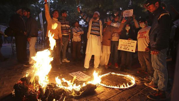 Protestors shout slogans as they burn an effigy of the juvenile convicted in the Delhi Gange rape case during a protest on the third anniversary of the incident in New Delhi (AP)