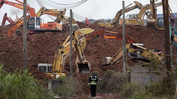 A policeman walks by the excavators digging the sea of soil to search for potential survivors following a landslide in Shenzhen (AP)