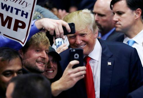 Republican presidential candidate Donald Trump poses with supporters after a campaign rally.