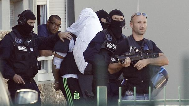 The suspect, centre, was arrested on June 28 (AP)