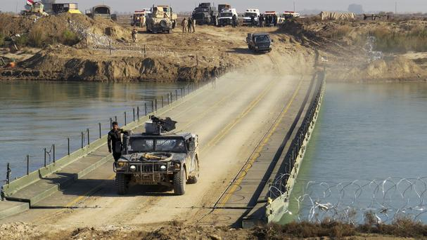 Iraqi security forces cross a bridge built by soldiers over the Euphrates River as they advance towards Ramadi (AP)