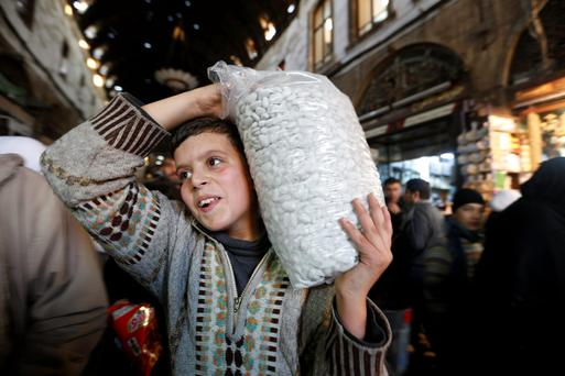 A boy carries a bag of sweets through a market on the occasion of Prophet Mohammad's birthday in Damascus, Syria, yesterday. Photo: Reuters