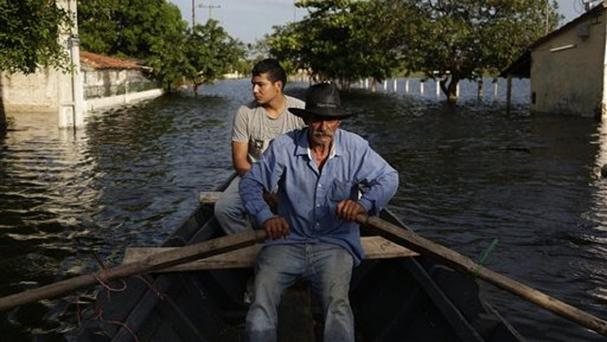 Victor Ferreira rows his boat through the streets of his Jukyty neighbourhood in Asuncion, Paraguay (AP)