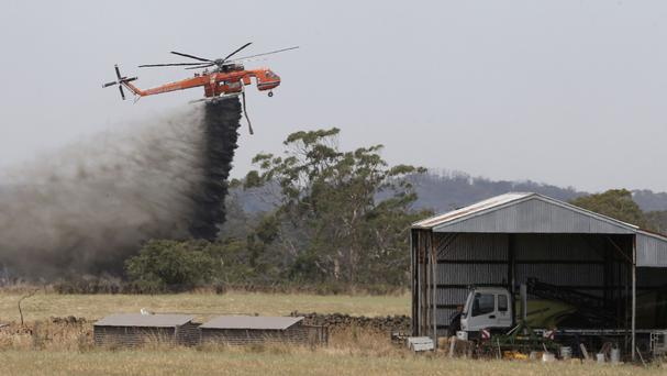 A Skycrane helicopter drops water as it works to hold back a wildfire from the hamlet of Claredon in Victoria (/AAP/AP)