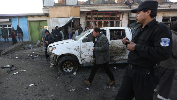 Afghan security forces inspect the site of a suicide car bomb attack near the Kabul airport (AP)