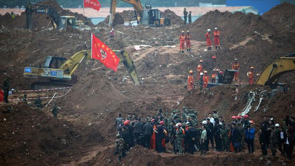 Government officials pictured on December 22 watching rescuers working following a landslide at an industrial park in Shenzhen (AP)