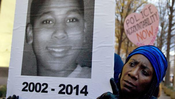 Protester Tomiko Shine holds a picture of Tamir Rice during a demonstration last year (AP)
