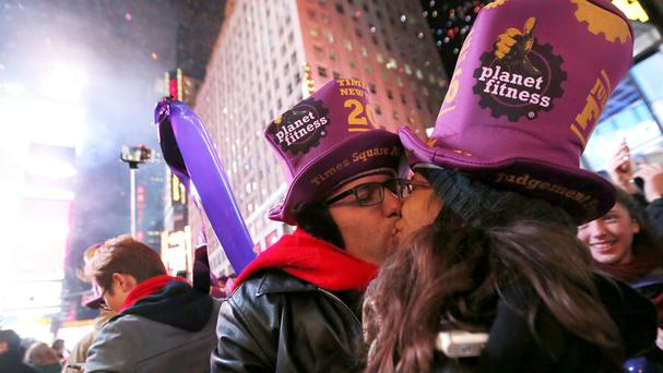 Israelis Omri Benzkry and Margarita Gankin share a New Year kiss in Times Square, New York (AP)
