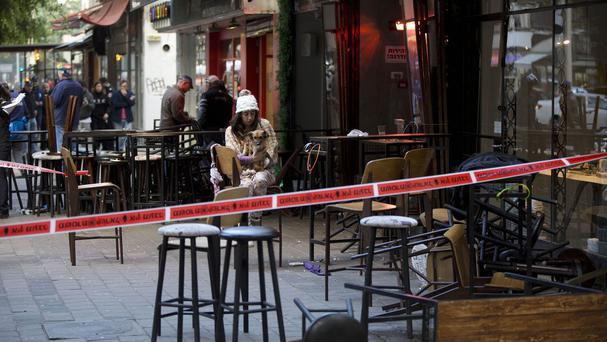 An Israeli eye witness sits with her dog at the scene of a shooting attack in Tel Aviv (AP)