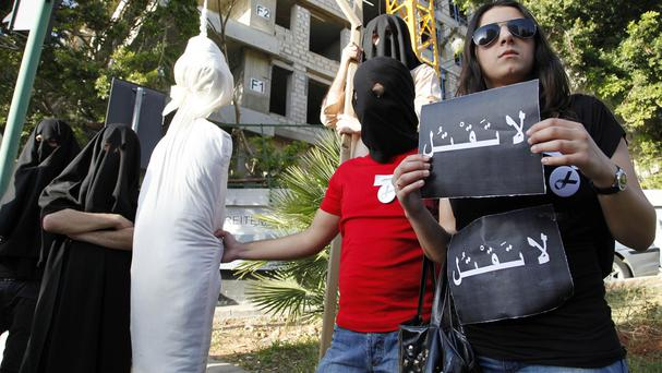 Activists re-enact an execution scene in front of the Saudi Arabia Embassy in Beirut, Lebanon, as they protest a possible beheading (AP)