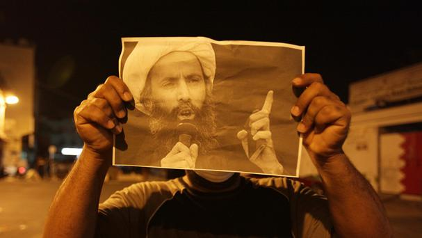 A protester holds up a picture of Saudi Sheikh Nimr al-Nimr (AP)