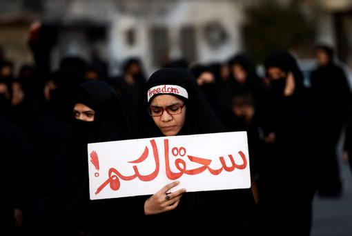 DEEPENING RELIGIOUS DIVIDE: A Bahraini woman in a silent protest against the execution of cleric Nimr al-Nimr (inset, right) by Saudi Arabia. The writing in Arabic reads: 'Damn you.' Photo: Mohammed al-Shaikh