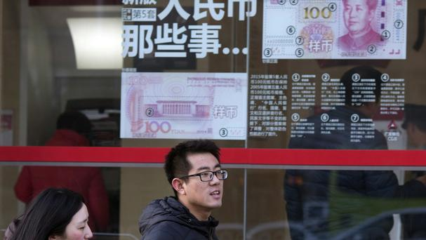 People walk past a display showing the new 100 Yuan note in Beijing after a plunge in Chinese stocks (AP)