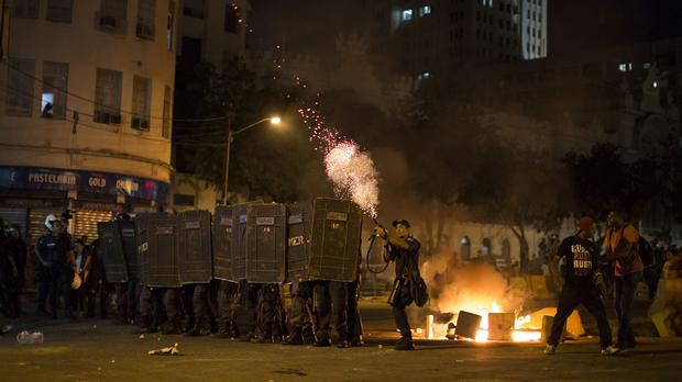 A police officer fires tear gas toward protesters during a march against bus fare hikes in Rio de Janeiro (AP)