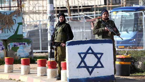 Israeli soldiers stand guard at a West Bank checkpoint (AP)