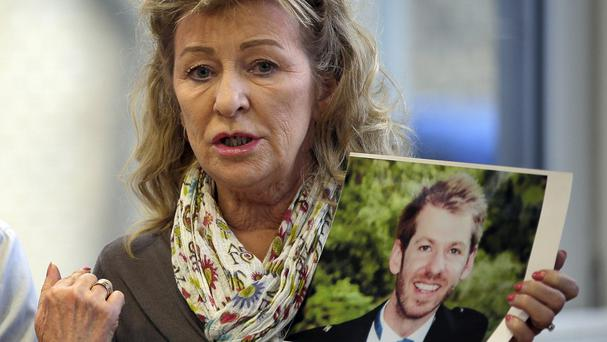 Rita Holland holds a picture of her son, Luke, during a press conference in Berlin. (AP)